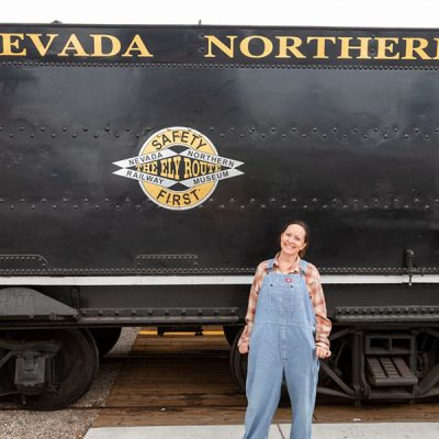 Women in overalls next to railroad train at The Northen Nevada Railway Museum The Ely Route